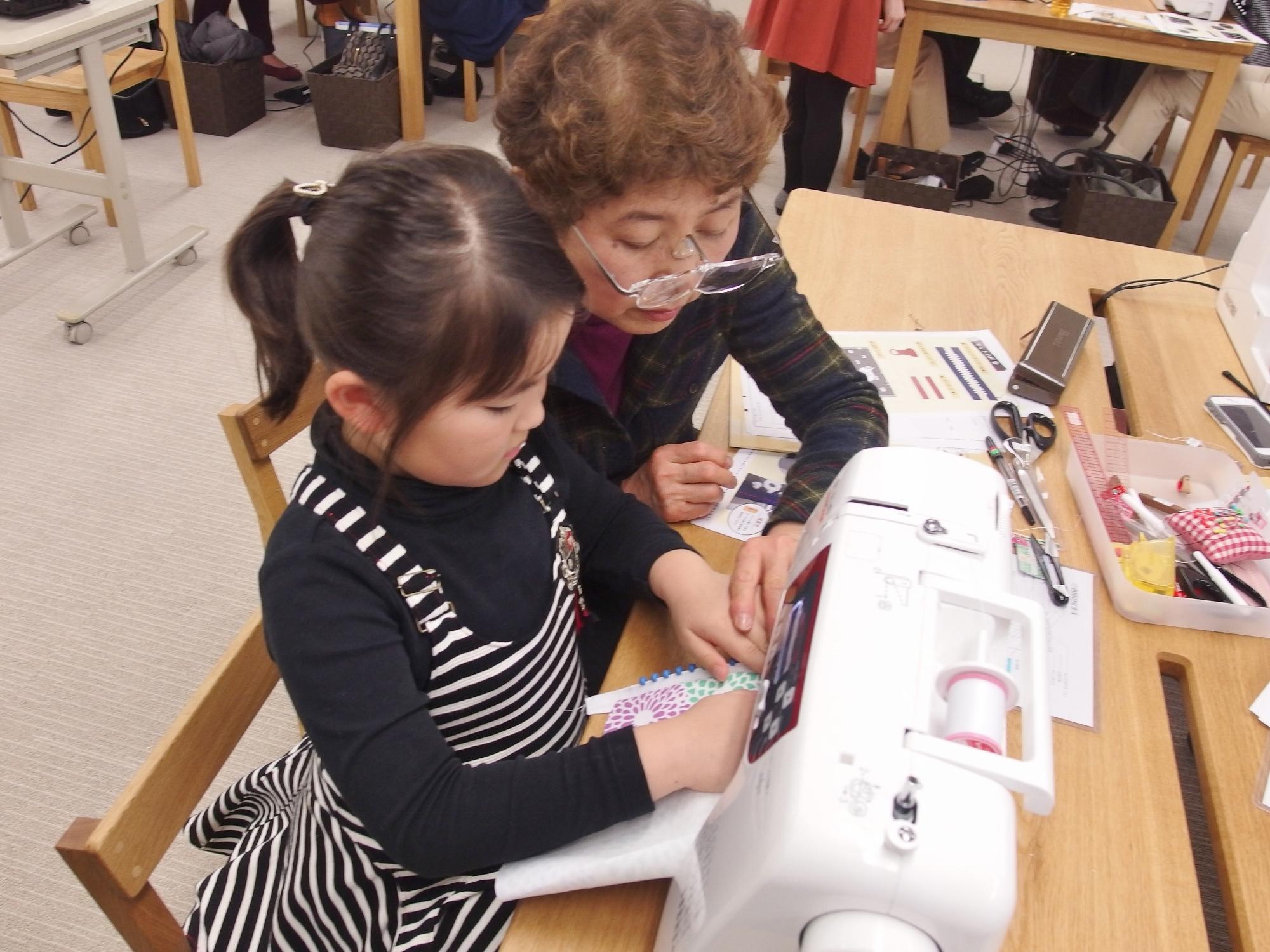 おばあちゃんと一緒に裁縫を楽しむ小学生